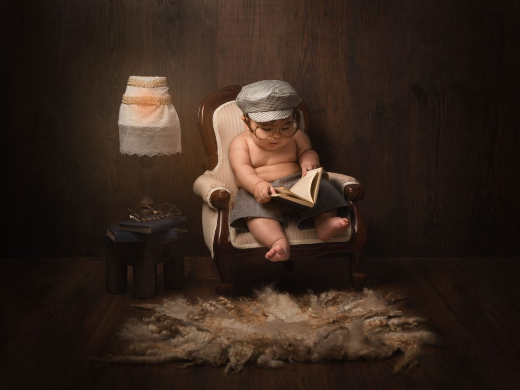 baby sitting with cap reading fine art photography