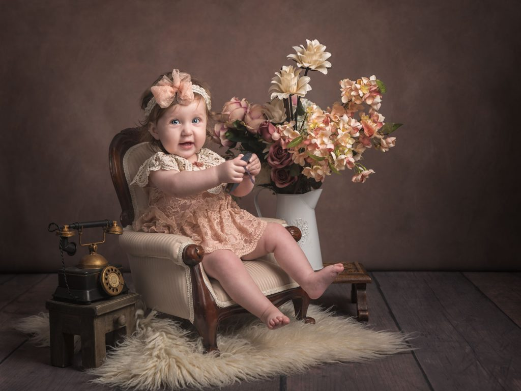 baby sitting in an old fashioned chair - fine art photography