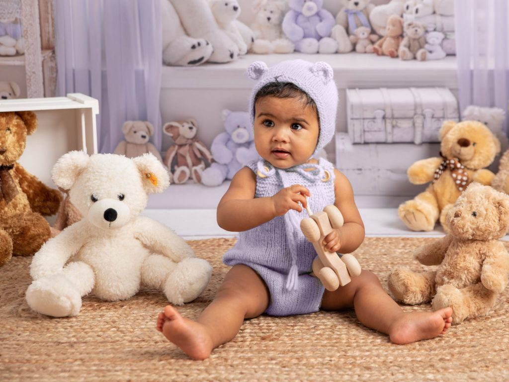 stunning baby sitting up in a bear costume