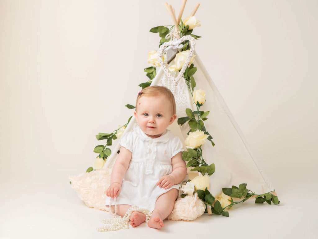 baby sitting up with white theme