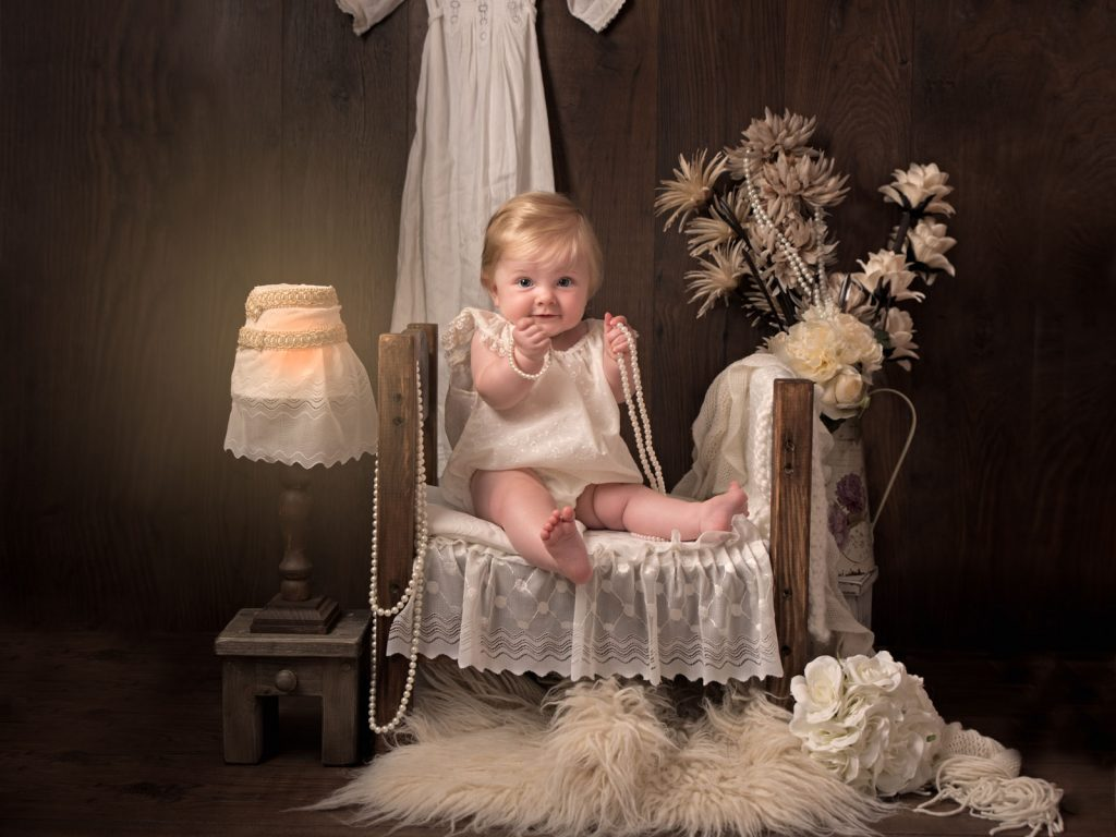 baby sitting in bed with nightgown and pearls