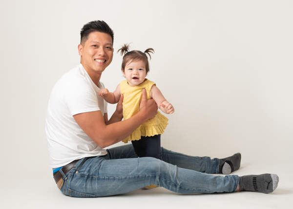dad holding his toddler daughter up for professional photoshoot