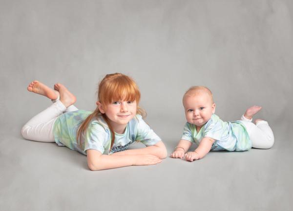 lying down looking at camera both young girl and baby