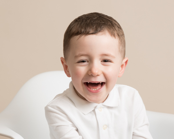 little boy smiling in white chair