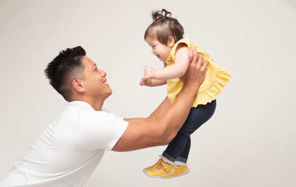 dad stretching his arms out in play with his daughter