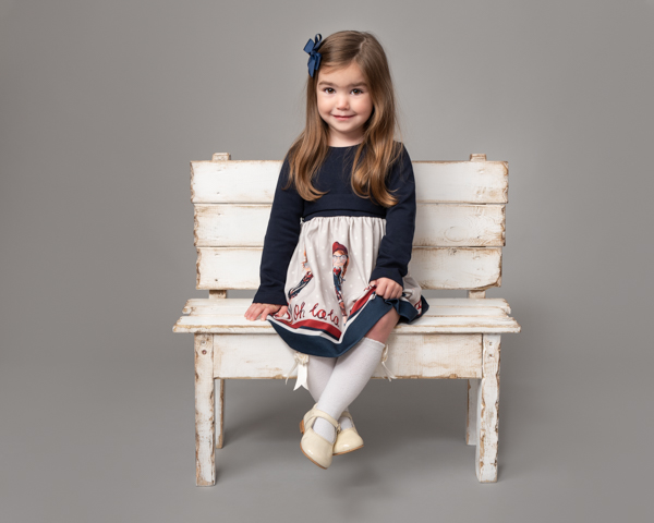 little girl with blue bow on white bench
