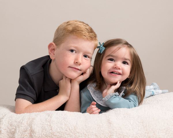 young boy and his younger sister lying down together