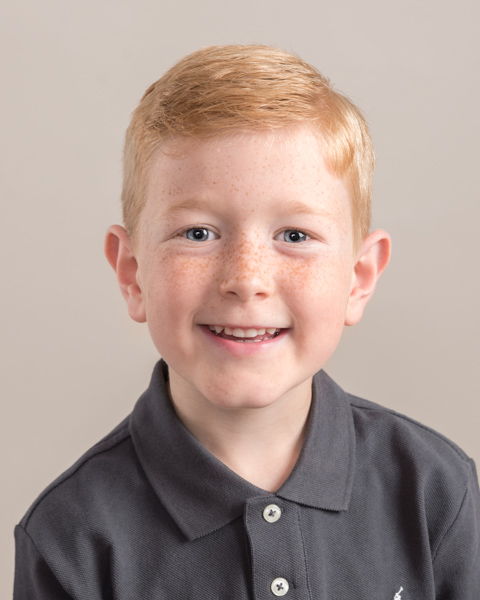 close up of young boy sitting with smart clothing