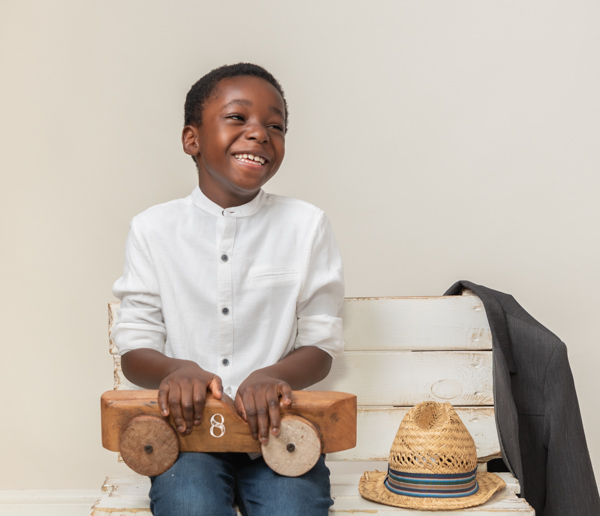 boy with his straw hat by his side stunning photoshoot