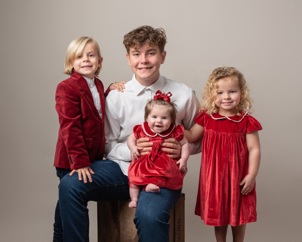 red themed family photoshoot with beautiful baby girl in the center