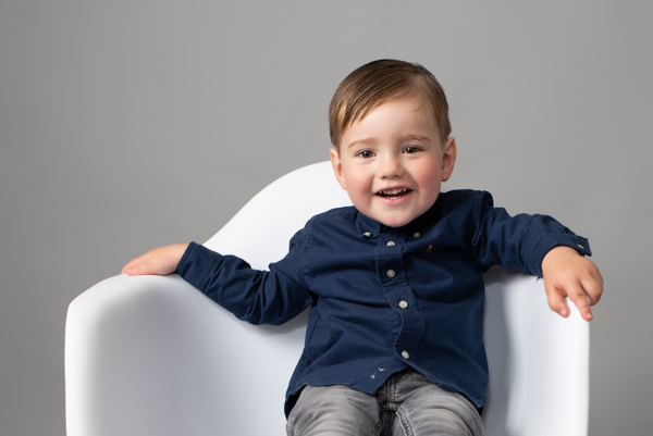 young boy with blue shirt sat in white chair