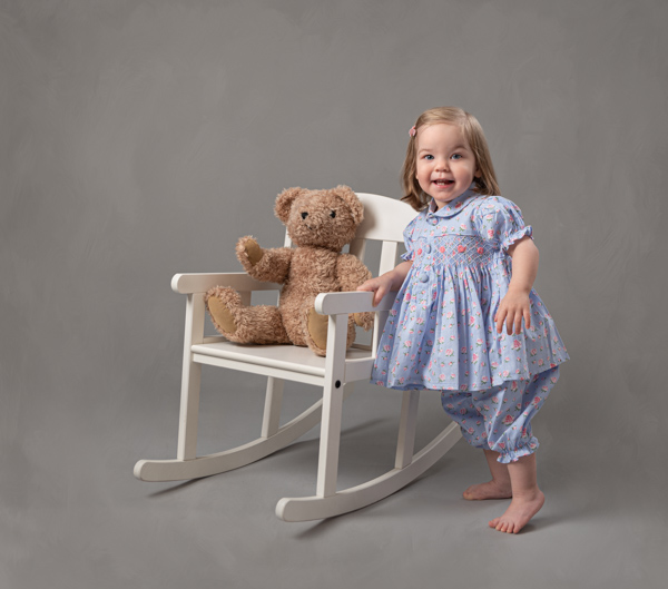little girl with her teddy sat in a chair