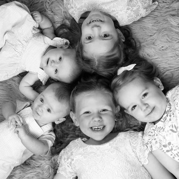 family of babies and young ladies in black and white