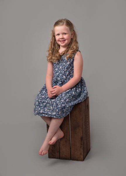 young girl sat on crate