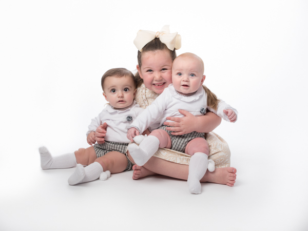 really happy girl with bow holding her siblings