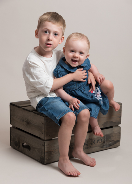two little children sitting on a crate