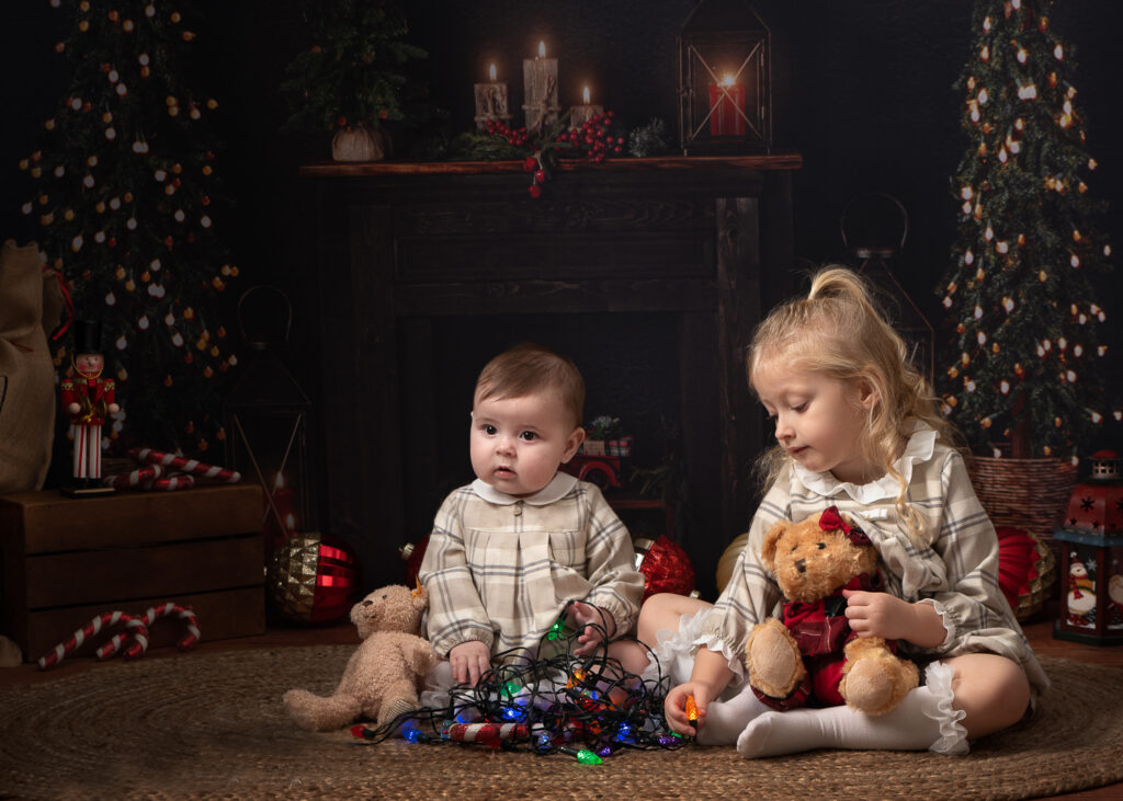 Two cute sisters in matching outfits sitting on floor with fairy lights