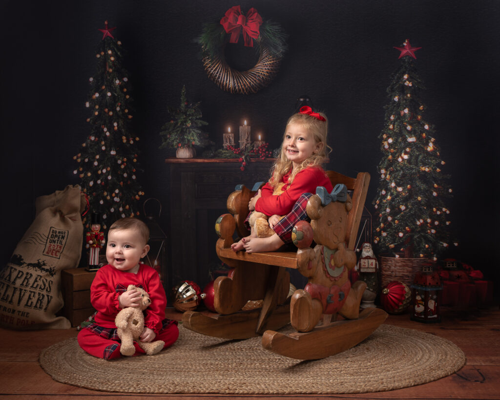 girl on rocking hair in Christmas pyjamas cuddling teddy with her baby sister sitting on the floor with teddy