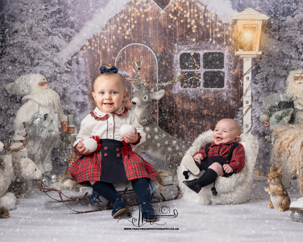 baby and sister in matching Spanish check outfits in the snow holding snowballs