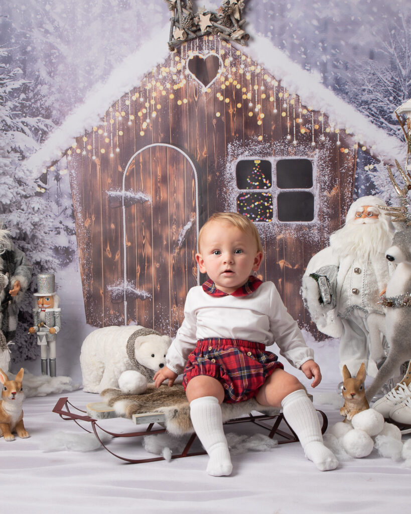 Cute baby on sledge with polar bear and Santa