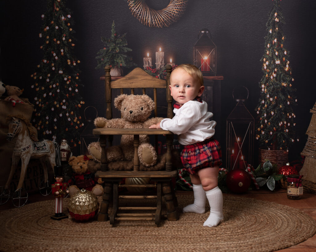 Baby in Spanish Christmas outfit standing with teddy in wooden highchair