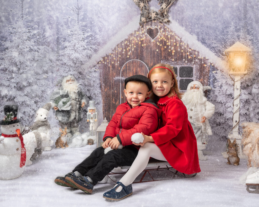 Brother and sister on sleigh in the snow photo shoot