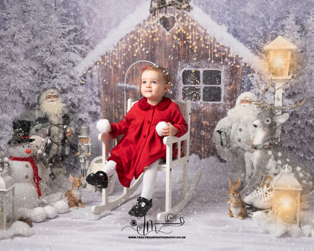 Little girl in red smart coat on white rocking chair holding snowballs in the snow photo