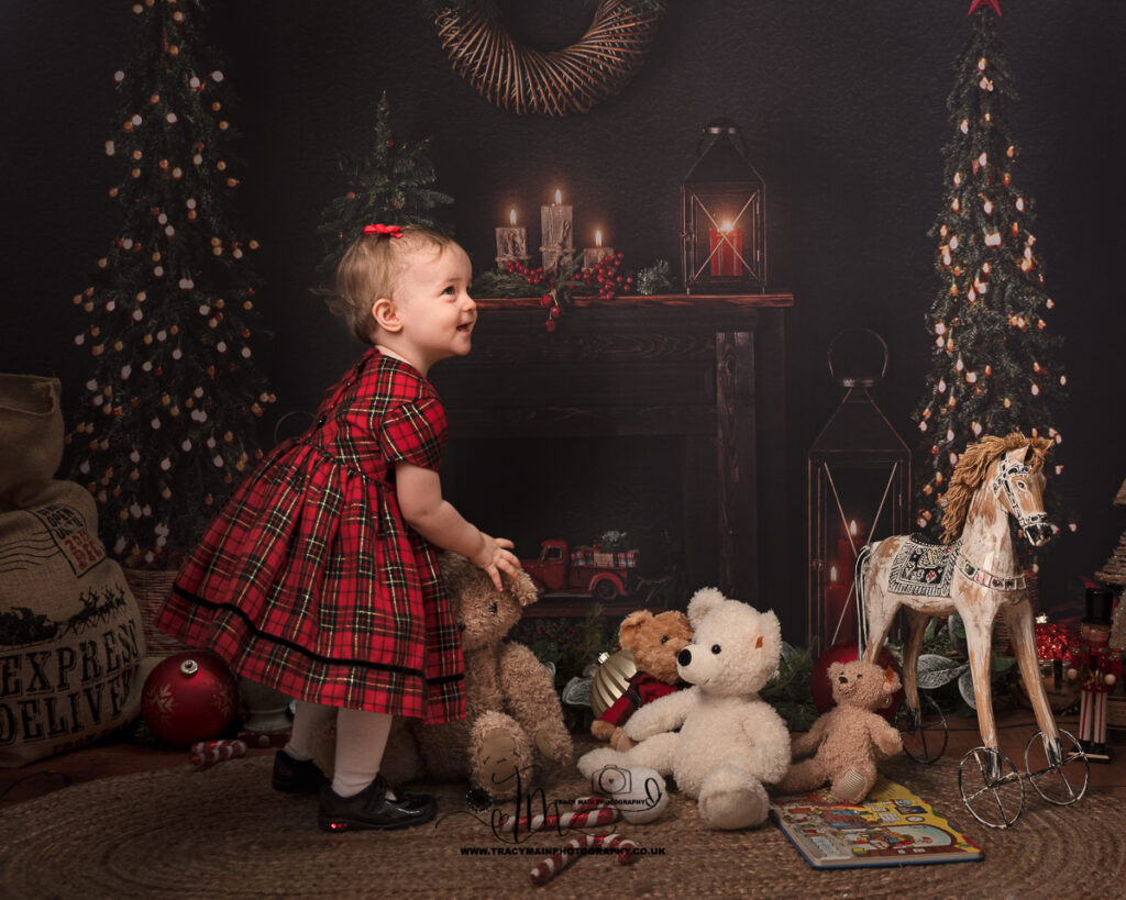 Little girls in check red Christmas dress in front or fire with teddy