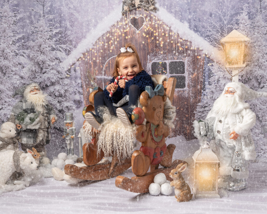 cute girl sitting on rocking chair in snow scene holding a candy cane