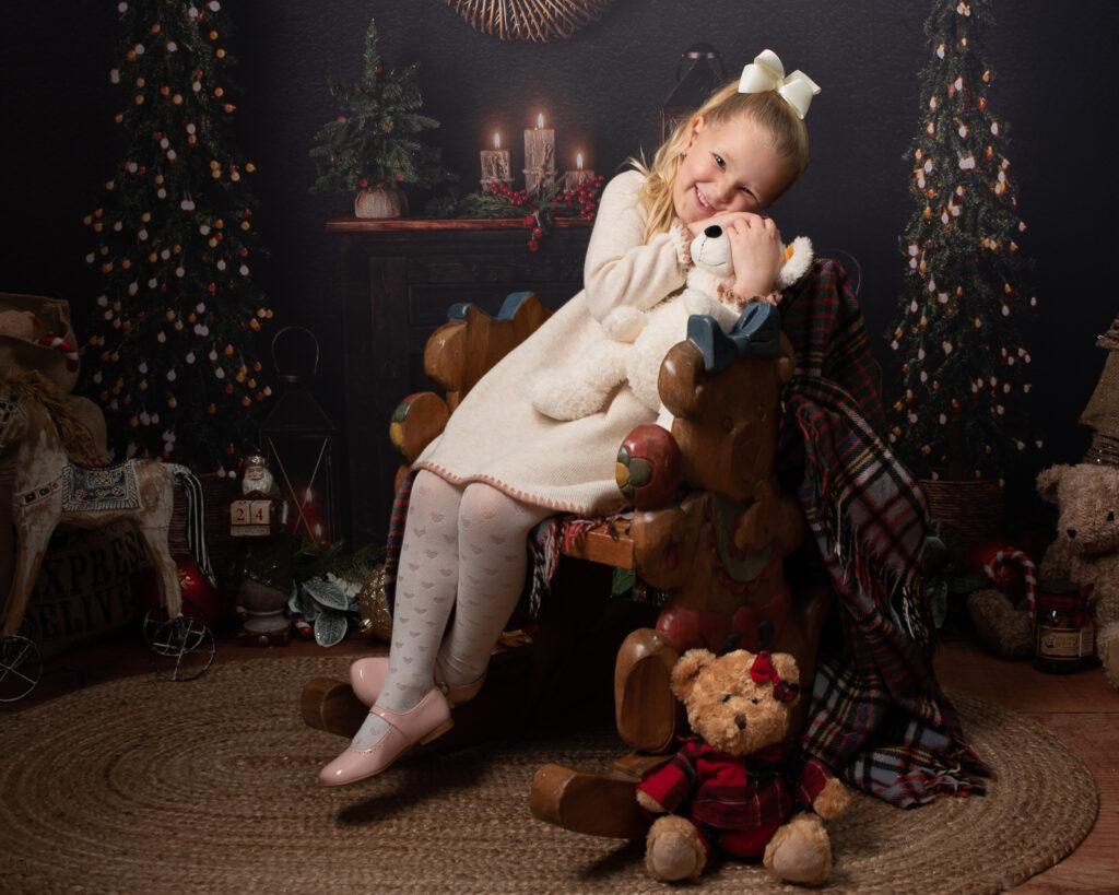 Cute girl cuddling teddy in Christmas photoshoot