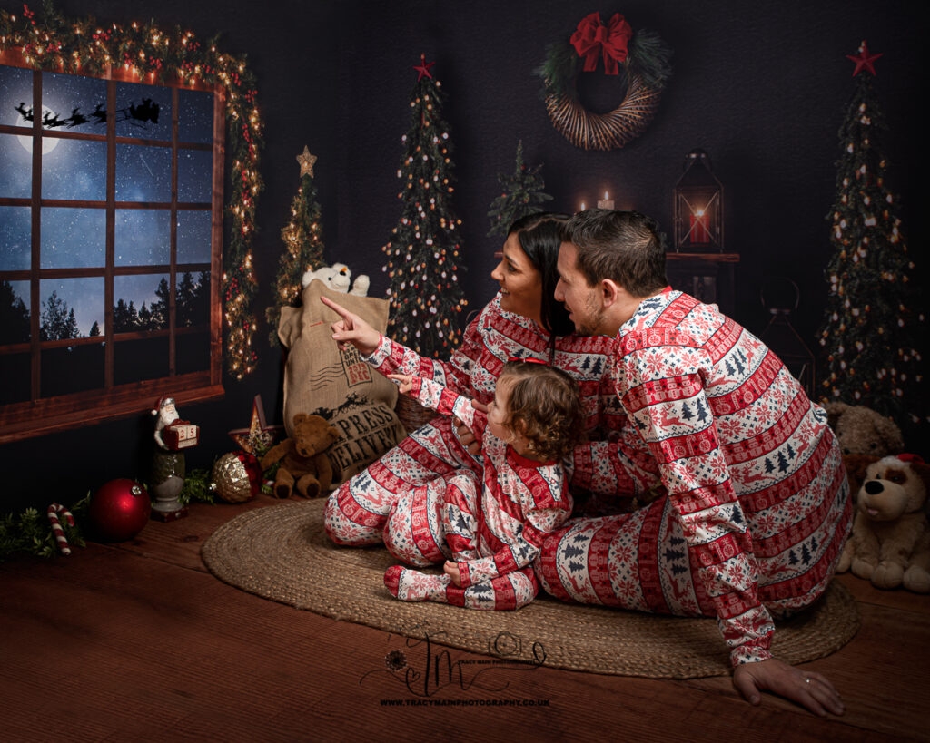 Family in matching pyjamas on Christmas Eve looking for Santa through the window