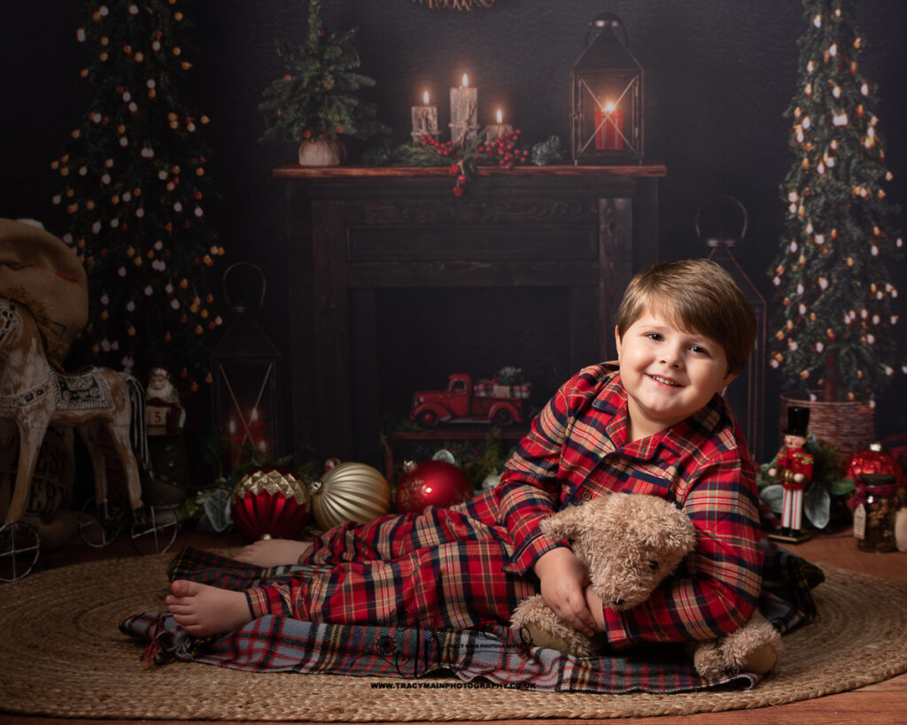 Christmas photo shoot boy in pyjamas in front of a fire