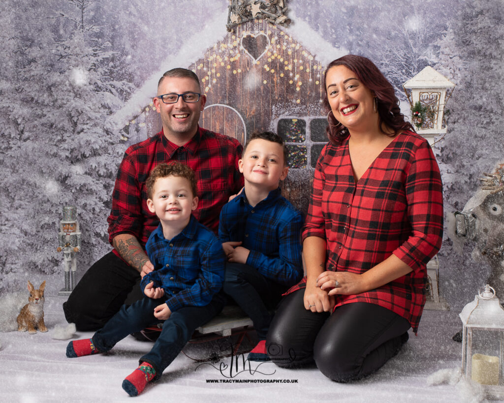 Christmas picture of family with two young boys in check shirts with parents in the snow