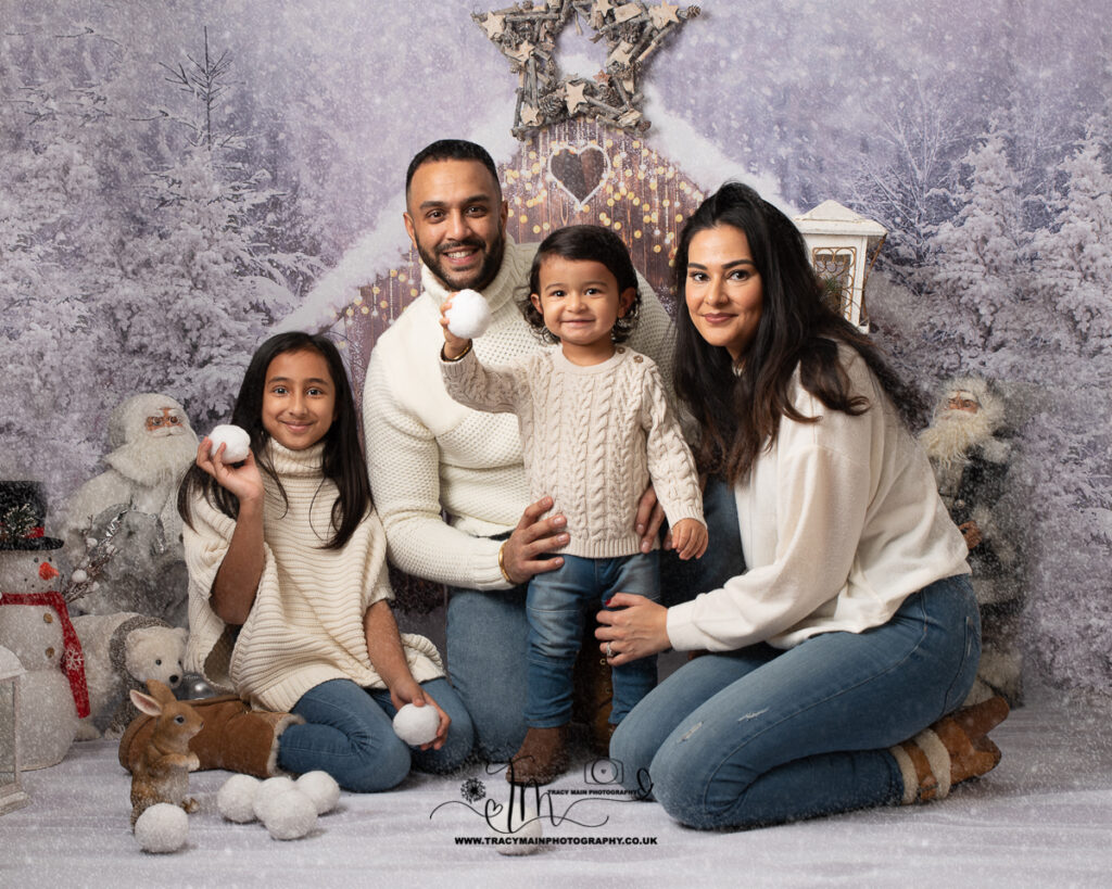 Christmas family photoshoot all wearing chunky aran knits with snowballs