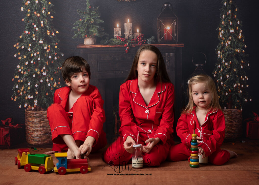 Three siblings in matching Christmas red pyjamas sitting on the floor in front of fire