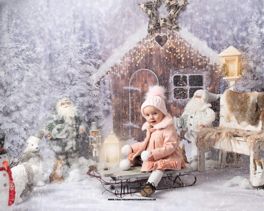 Little girl in pink pom pom hat on sledge photo shoot
