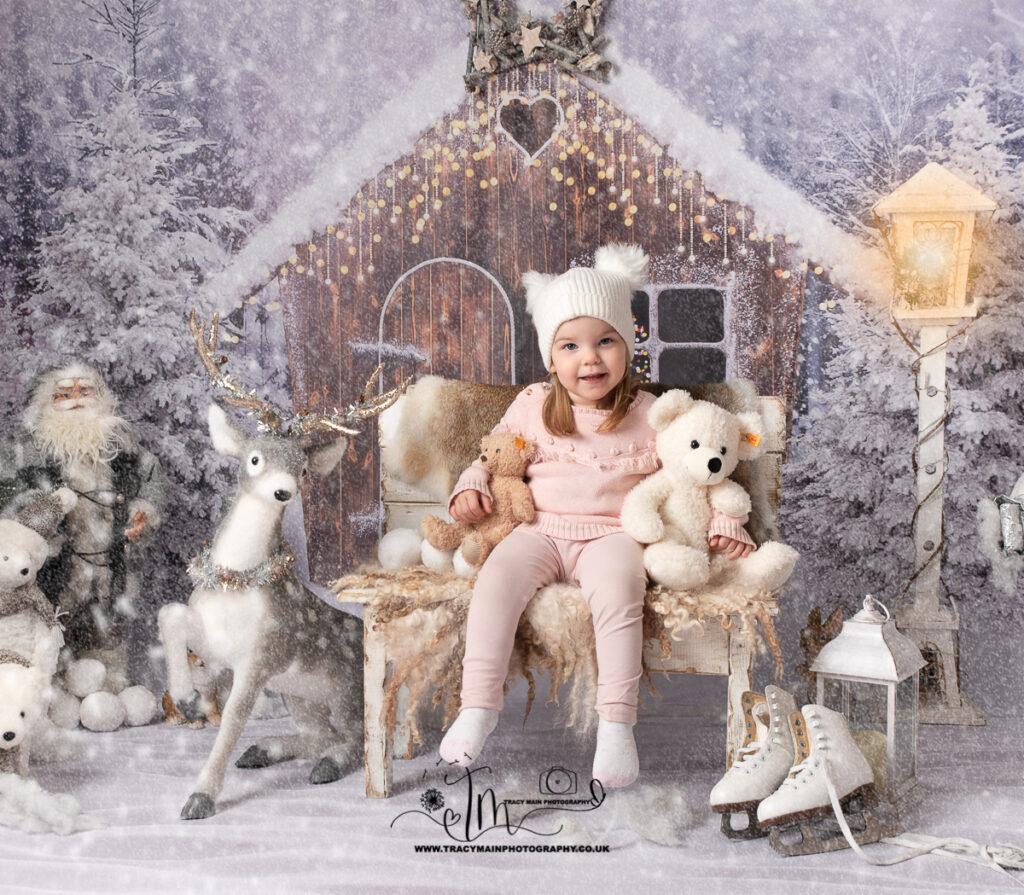 girl on bench in pom pom hat cuddling teddies in the snow