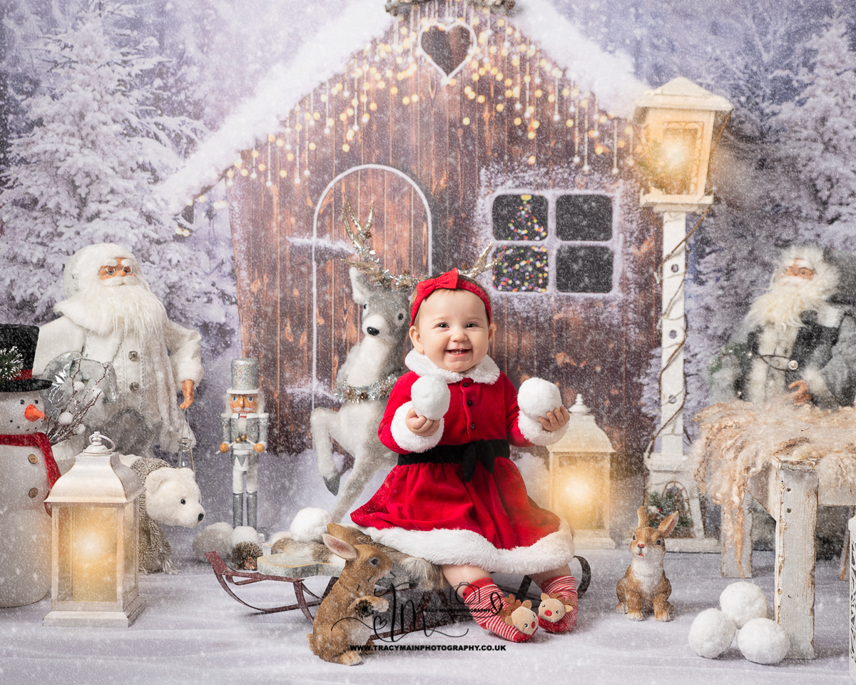 Little baby on sledge in father Christmas outfit holding snowballs
