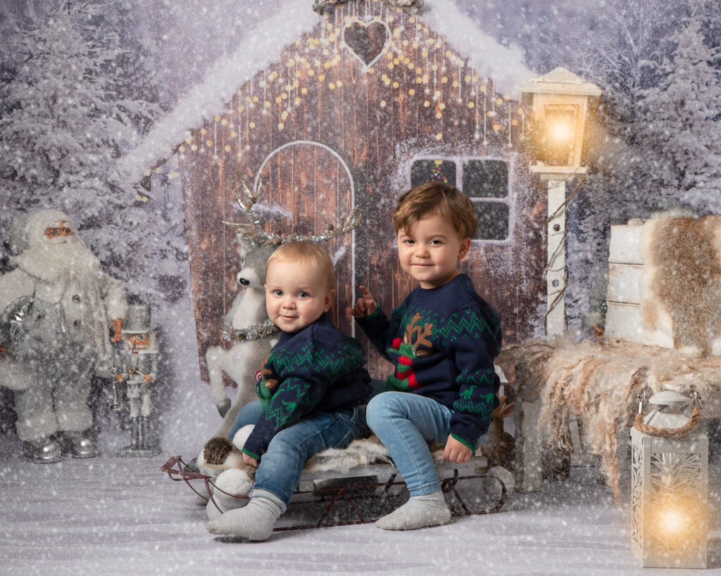 Two brothers in Christmas jumpers on ledge photo shoot